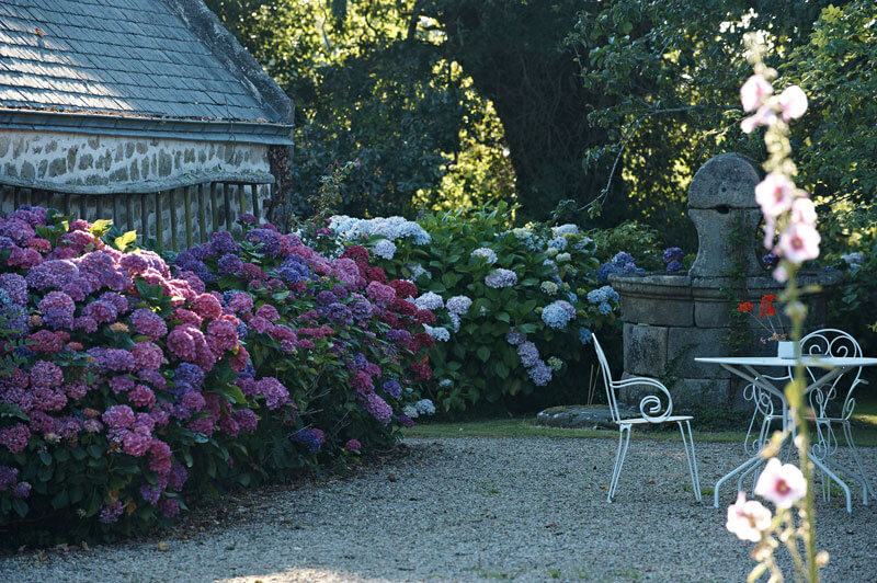 Jardin ferme de kerscuntec chaises et table en fer blanc fontaine en pierre hortensias
