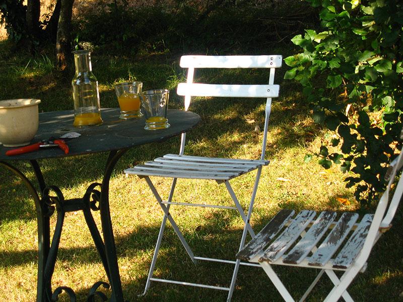 Chaises et table jus d'orange dans le jardin de la Ferme